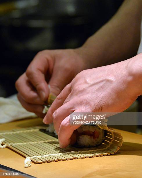 This photo taken on July 16 2013 shows a chef and restaurant owner preparing roll sushi for a customer at a highend sushi restaurant in Tokyo There...