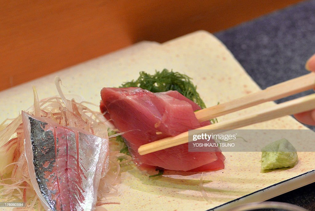 This photo taken on July 16 2013 shows a customer eating bonito and horse mackerel sashimi at a highend sushi restaurant in Tokyo There is no menu...