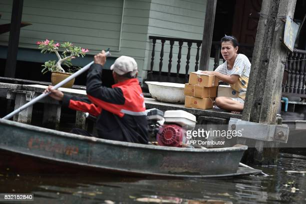 TOPSHOT This photo taken on July 17 2017 shows a resident speaking to postman Nopadol Choihirun as he delivers mail in the Bang Khun Thian district...