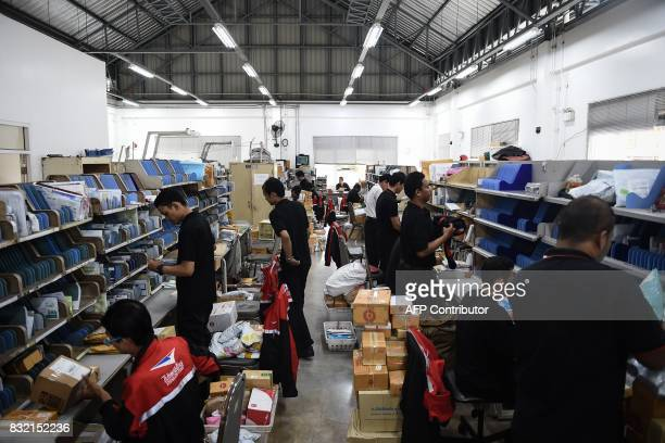 This photo taken on July 17 2017 shows people working at the Bang Khun Thian post office on the outskirts of Bangkok which also provides services to...