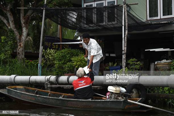 This photo taken on July 17 2017 shows postman Nopadol Choihirun delivering mail by boat in the Bang Khun Thian district on the outskirts of Bangkok...