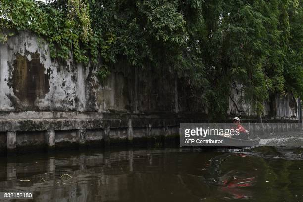 This photo taken on July 17 2017 shows postman Nopadol Choihirun steering his boat through the canal as he delivers mail in the Bang Khun Thian...