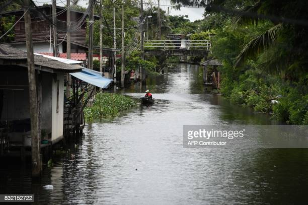 This photo taken on July 17 2017 shows postman Nopadol Choihirun steering his boat through the canal in the Bang Khun Thian district on the outskirts...