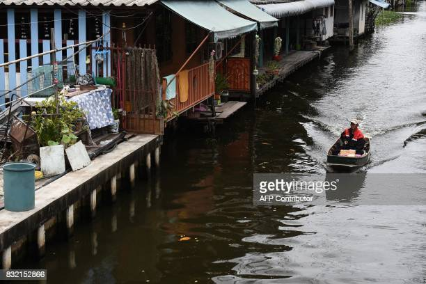 This photo taken on July 17 2017 shows postman Nopadol Choihirun steering his boat past houses along the canal in the Bang Khun Thian district on the...
