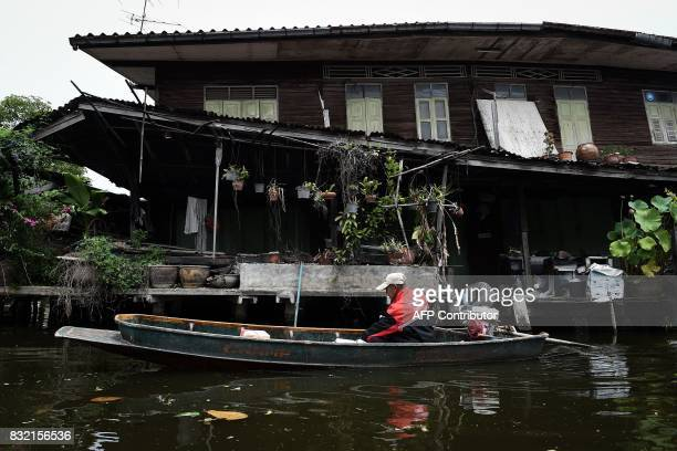 This photo taken on July 17 2017 shows postman Nopadol Choihirun steering his boat past an old house on the canal as he delivers mail in the Bang...