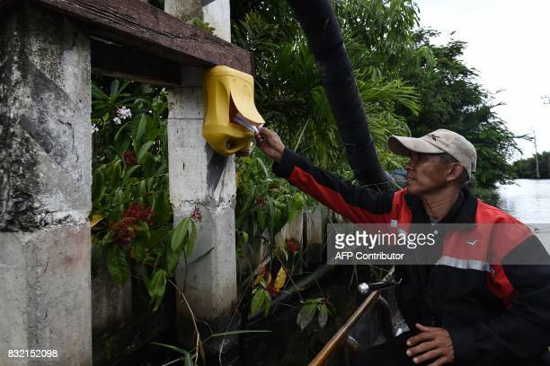 TOPSHOT This photo taken on July 17 2017 shows postman Nopadol Choihirun putting mail in a postbox along the canal in the Bang Khun Thian district on...