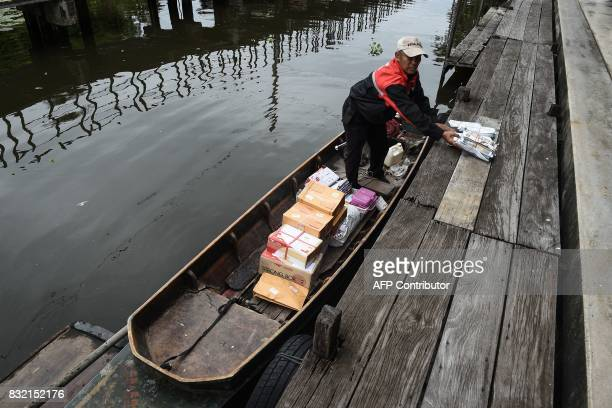 TOPSHOT This photo taken on July 17 2017 shows postman Nopadol Choihirun loading parcels and mail into a boat on the canal in the Bang Khun Thian...