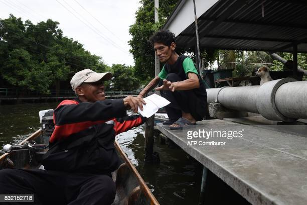 This photo taken on July 17 2017 shows postman Nopadol Choihirun delivering mail to a resident in the Bang Khun Thian district on the outskirts of...