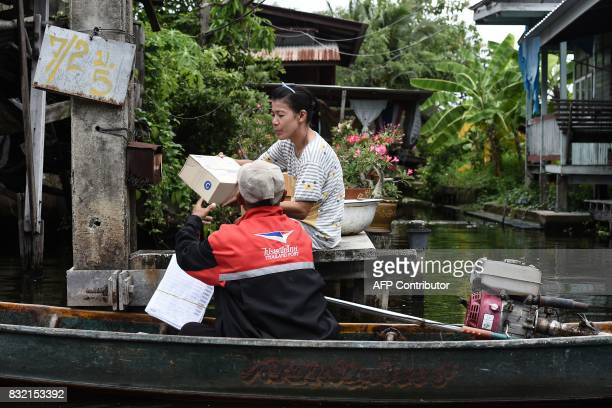 This photo taken on July 17 2017 shows postman Nopadol Choihirun delivering parcels to a resident in the Bang Khun Thian district on the outskirts of...