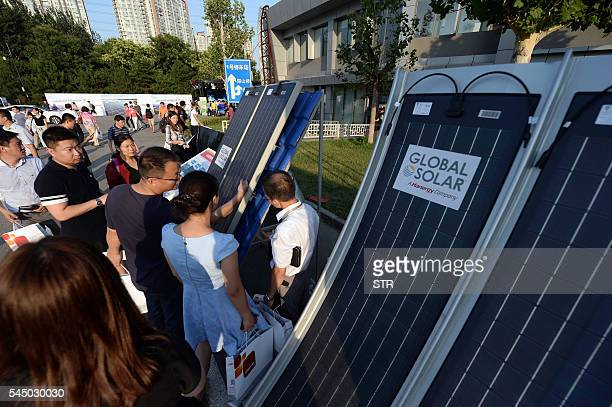 This photo taken on July 2 2016 shows people looking at solar panels during a launch event of Hanergy's solarpowered car in Beijing Thinfilm power...