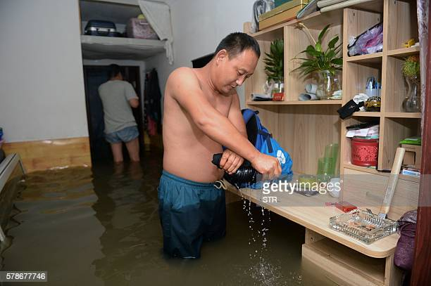 This photo taken on July 21 2016 shows a man drying his clothes as he stands in a flooded room in Changping District in Beijing Torrential rain...