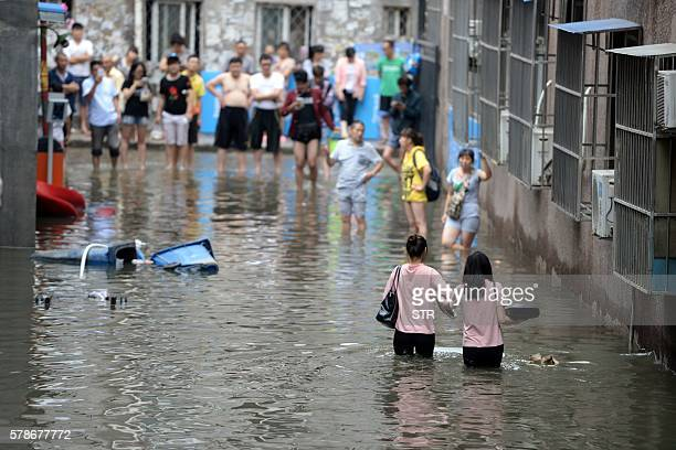 This photo taken on July 21 2016 shows people making their way through a flooded area in Changping District in Beijing Torrential rain lashing...