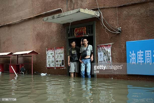 This photo taken on July 21 2016 shows two residents standing in a flooded area in Changping District in Beijing Torrential rain lashing northern...