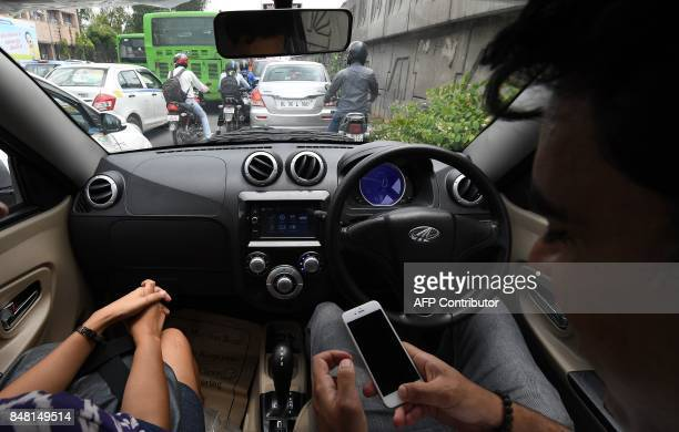 This photo taken on July 21 2017 shows Ankur Bhatia head of marketing at Mahindra Electric Mobility checking his mobile while driving Mahindra's...