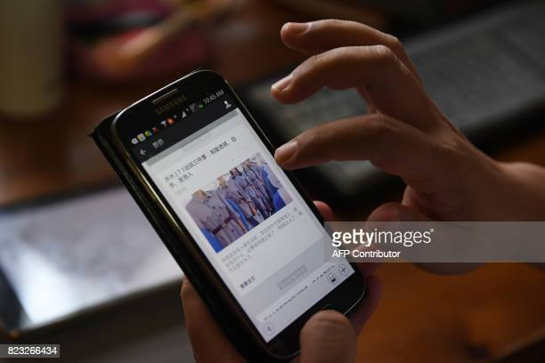 This photo taken on July 21 2017 shows writer and former professor Qiao Mu displaying one of his posts on a mobile phone at his home in Beijing When...