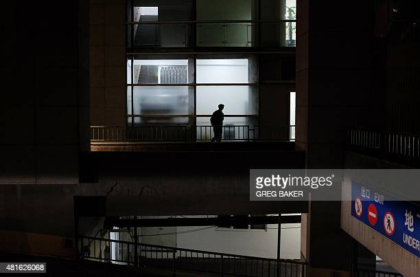 This photo taken on July 22 2015 shows a security guard patrolling in a residential and commercial building in Beijing China's National Bureau of...