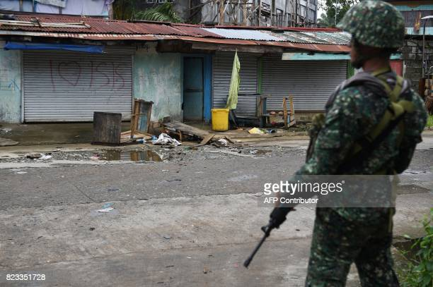 This photo taken on July 22 2017 shows a Philippine soldier standing in front of a graffiti in a deserted neighbourhood in Marawi Western governments...