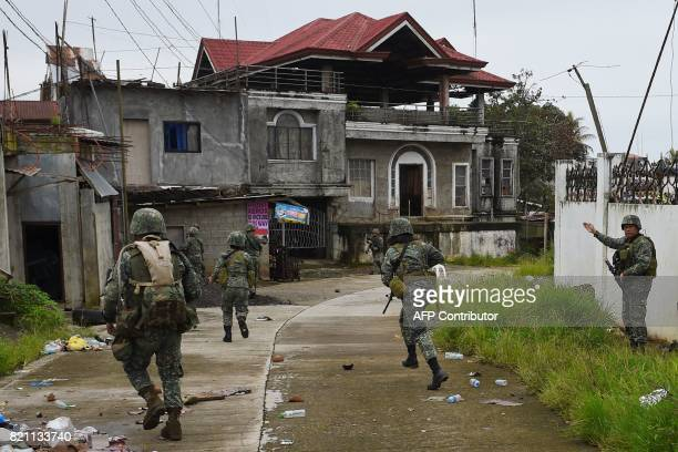 This photo taken on July 22 2017 shows Philippine Marines taking cover from sniper fire while on patrol at the frontline in Marawi on the southern...