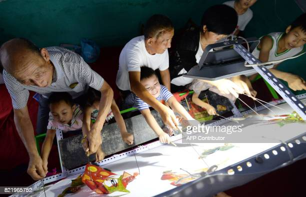 This photo taken on July 24 2017 shows a group of volunteers from a shadow art troupe teaching 'leftbehind' children how to operate shadow puppets in...