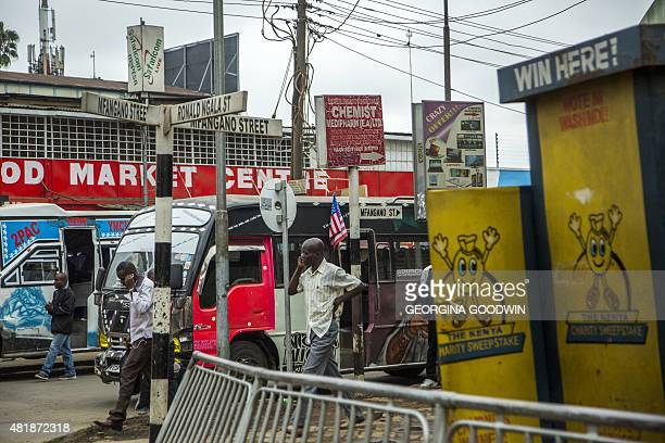 This photo taken on July 25 2015 shows men walking down a street next to a bus adorned with US flags in Nairobi US President Barack Obama arrived in...
