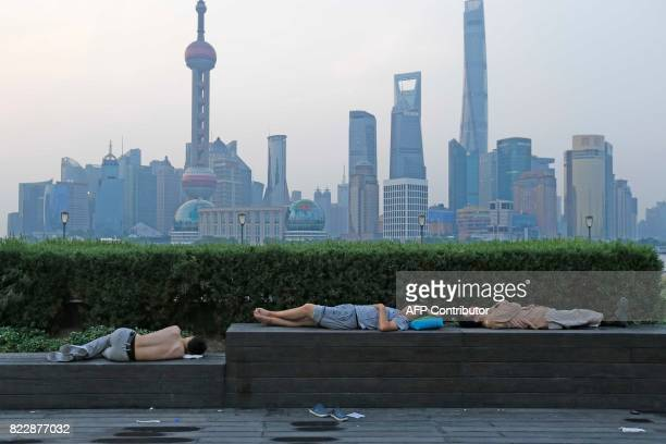 TOPSHOT This photo taken on July 25 2017 shows people sleeping on the waterfront bund to keep cool in Shanghai Parts of China including Shanghai have...