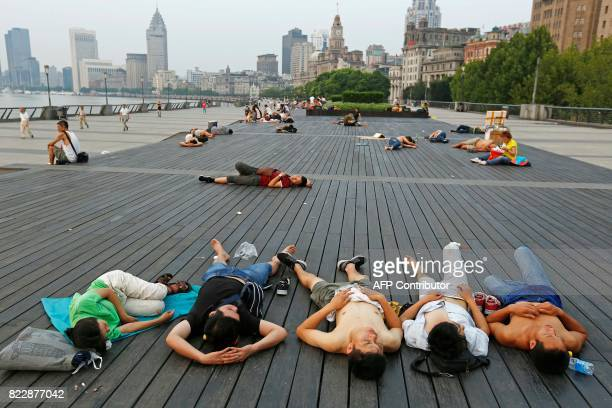 This photo taken on July 25 2017 shows people sleeping on the waterfront bund to keep cool in Shanghai Parts of China including Shanghai have seen...
