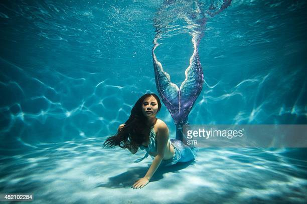 This photo taken on July 26 2015 shows a woman clad in her selfmade mermaid costume swimming in a pool in China's southwest Chongqing municipality...