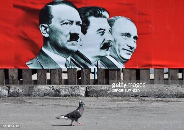 This photo taken on July 28 2014 shows a placard depicting Adolf Hitler Joseph Stalin and Russian President Vladimir Putin displayed on the Maidan...