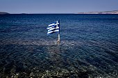 This photo taken on July 29 2015 shows a Greek flag floating in the sea at the Kalamitsa beach on Skyros island Greece expects debt reduction from...