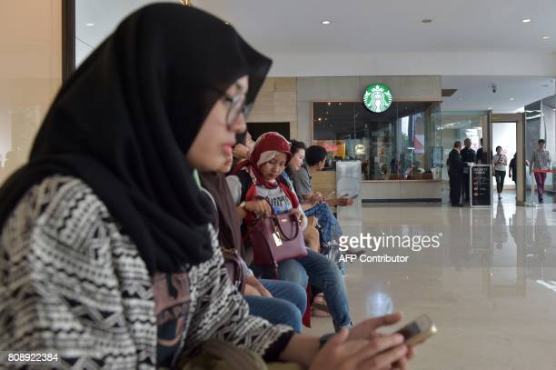 This photo taken on July 4 2017 shows Indonesian Muslim women sitting outside a Starbucks cafe at a shopping mall in Jakarta Muslims in Indonesia and...