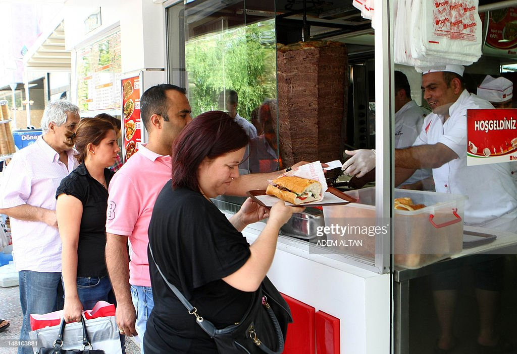 This photo taken on July 4, 2012, in Ankara shows people buying sandwiches at a local kebab reastaurant. In Turkey 35% of the population has accumulated excess body fat to the extent that it may have an adverse effect on health, leading to reduced life expectancy and/or increased health problems. The Turkish health ministry has launched a campaign calling on Turks to be more active. AFP PHOTO/ADEM ALTAN