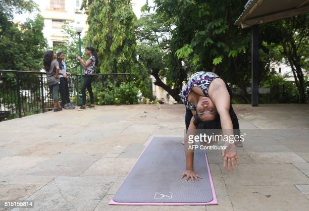 This photo taken on July 6 2017 shows Dolly Singh doing yoga at a park in Mumbai The plussized Indian woman is challenging body stereotypes and...
