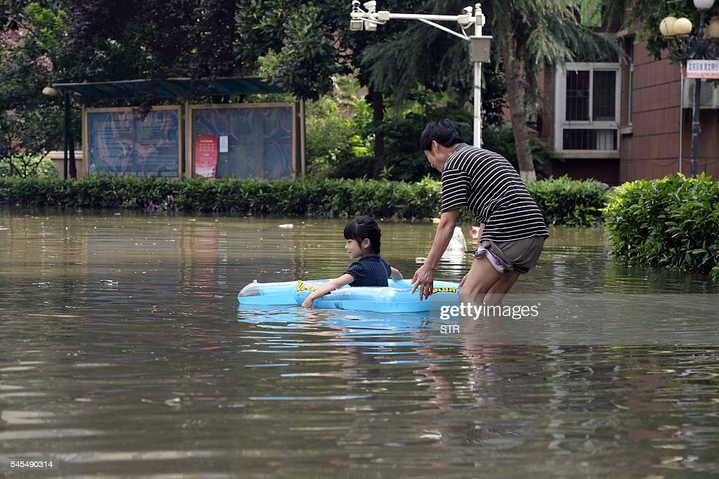 This photo taken on July 7 2016 shows a child using an inflatable device at a flooded housing estate in Wuhan in central China's Hubei province...
