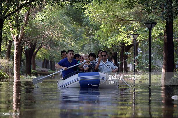 This photo taken on July 7 2016 shows residents making their way through a flooded street on an inflatable boat in Wuhan in central China's Hubei...