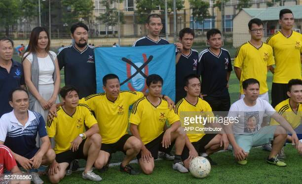 This photo taken on July 9 2017 shows members of the NoU FC squad posing before their weekly football match at a local pitch in Hanoi The team of...
