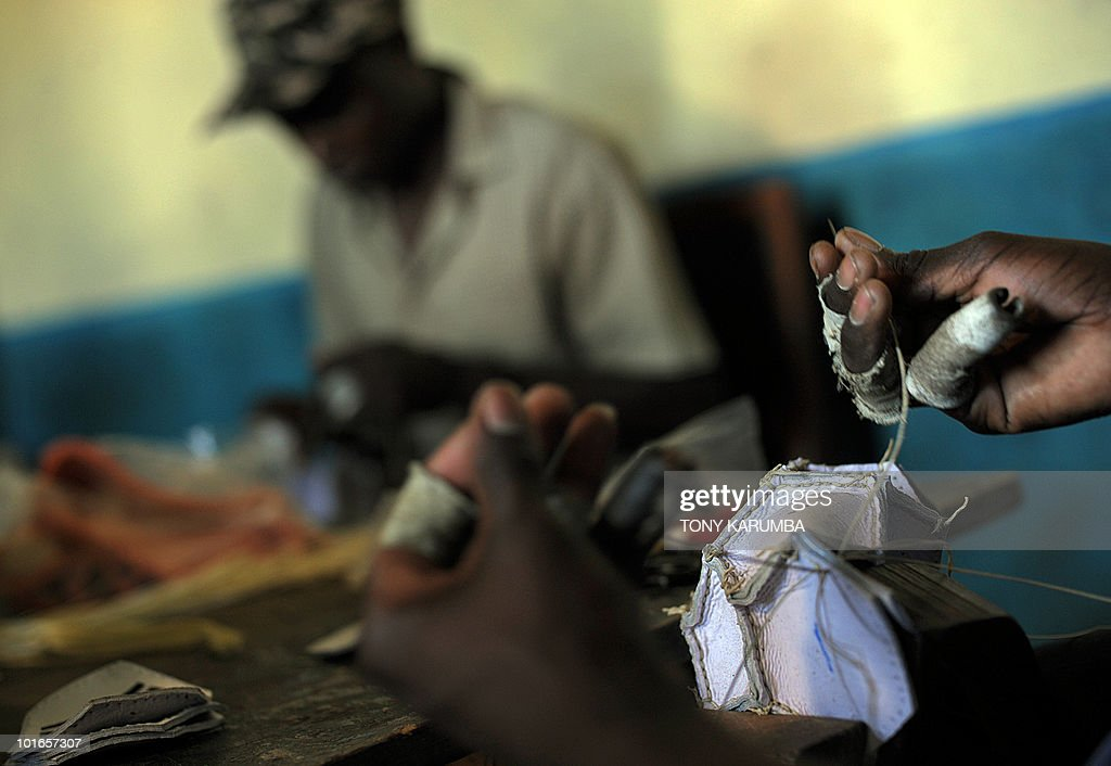 This photo taken on June 01, 2010 shows workers sewing soccer balls at a cottage industry near Kenya's Eldoret town [approximately 300 kilometres north of Nairobi]. One of the hardest hit areas of Kenya by the 2007/08 electoral violence that saw more than 1,500 killed in tribal animosity, soccer in Lugari, an area that borders Eldoret, is being harnessed as a platform to foster unity and reconciliation among local youth drawn from varied tribes of Kenyans that inhabit the area. An intiative by inspired local residents called 'Maliza umasikini, maliza ukabila', [end poverty, end tribalism in swahili] is struggling to draw together the area's youth through soccer matches with barely any funding, using locally made kits and balls to create youth soccer teams, an intiative that residents say has managed to whittle down pulpable tension and animosity among youth from various tribes in the area. AFP PHOTO/Tony KARUMBA