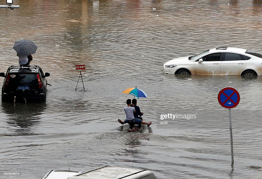 This photo taken on June 1 2016 shows two residents riding a scooter through a flooded street in Wuhan central China's Hubei province A heavy...