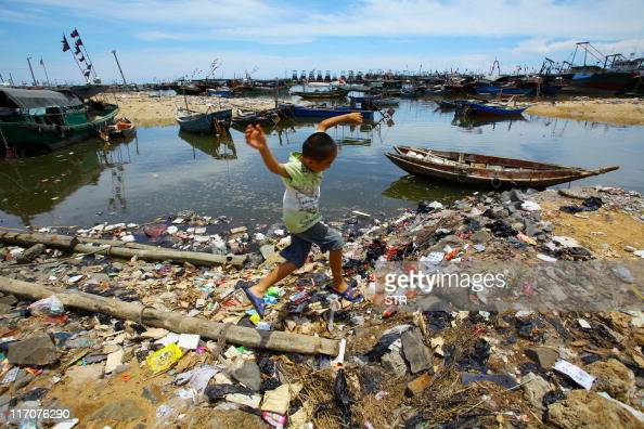 This photo taken on June 13 2011 shows a Chinese boy running along the rubbishstrewn beach along the sea coast in Anquan village south China's Hainan...
