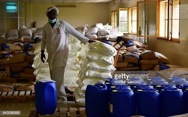 This photo taken on June 14 2016 shows an employee handling powder milk bags in the sugar milk and oil warehouse at the Societe de Transformation...