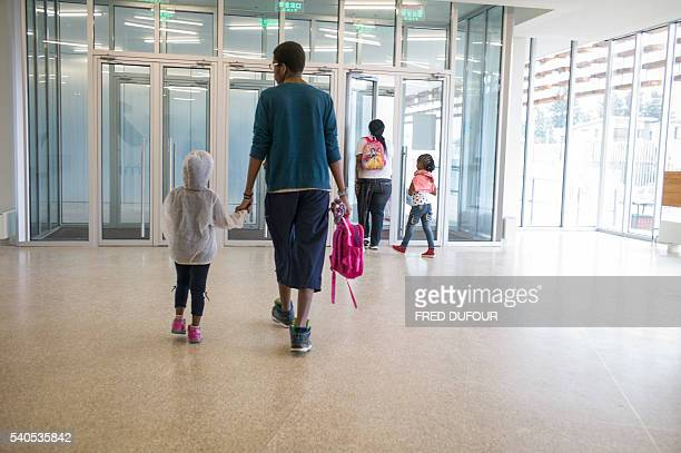 This photo taken on June 14 2016 shows mothers taking their kids home after school at the new International French School in Beijing / AFP / FRED...