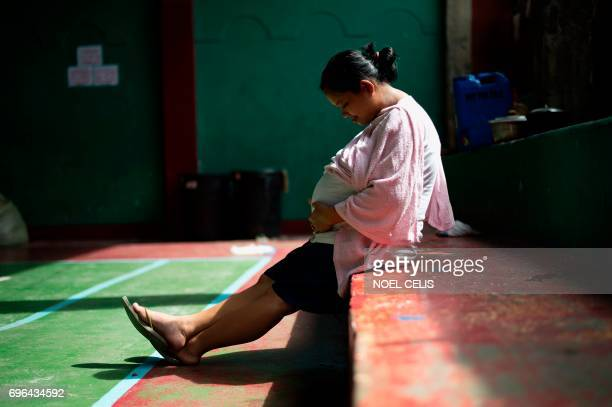 This photo taken on June 15 shows 9 months pregnant mother Rosalyne Arat at an evacuation center at the Buruon Barangay Hall in Iligan on the...