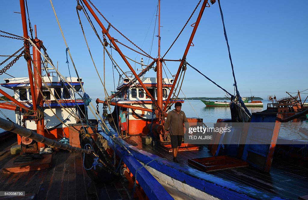 This photo taken on June 16 2016 shows a crew member of a reeffishing vessel walking along the bow as it is achored at the port of Masinloc in...