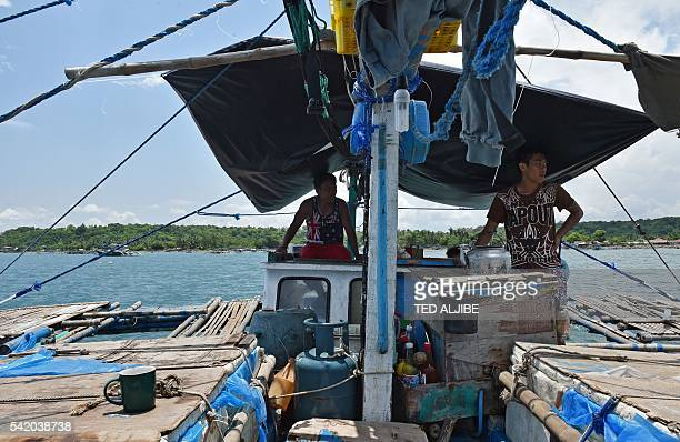This photo taken on June 16 2016 shows crew sitting inside their vessel anchored at the mouth of the South China Sea off the town of Infanta in...