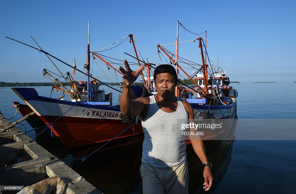 This photo taken on June 16 2016 shows Epifanio Marqueza one of the captains of a reeffishing fleet gesturing next to his vessel achored at the port...