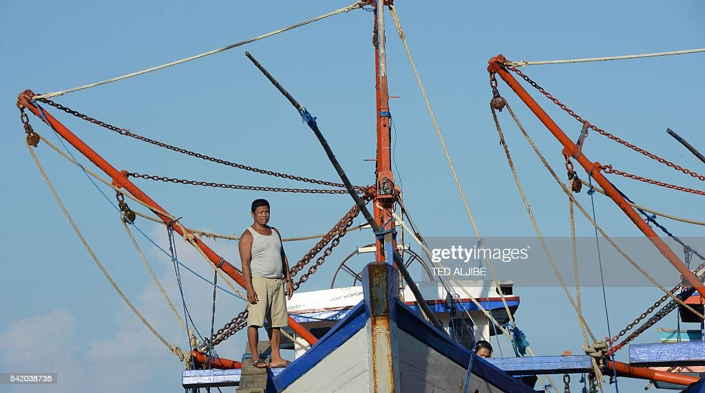 This photo taken on June 16 2016 shows Epifanio Marqueza one of the captains of a reeffishing fleet standing at the bow of his vessel achored at the...