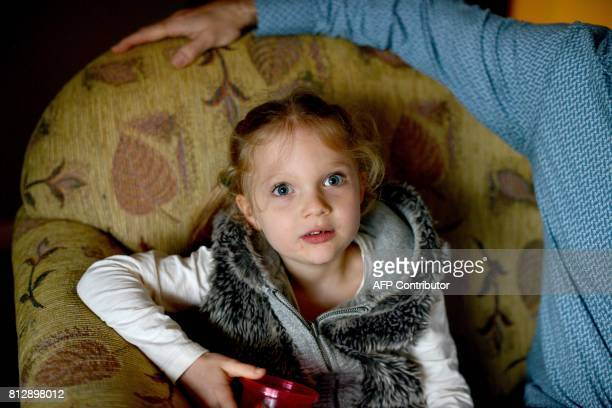 This photo taken on June 16 2017 shows fouryearold Arielle Harding sitting on the sofa with her father Tim at their home in Newcastle 160km north of...