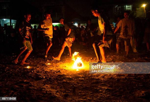 This photo taken on June 17 2017 shows youths playing fire football known locally as 'sepak bola api' at a slum area in Surabaya Indonesia's second...