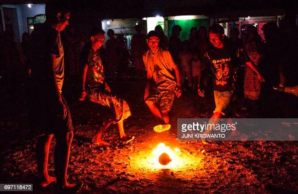 TOPSHOT This photo taken on June 17 2017 shows youths playing fire football known locally as 'sepak bola api' at a slum area in Surabaya Indonesia's...