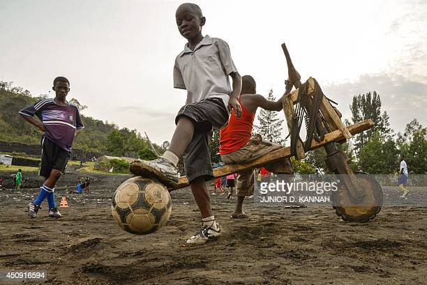 This photo taken on June 19 2014 in Goma shows young boys playing football during a training session at the local TFC Cheval blanc football school...