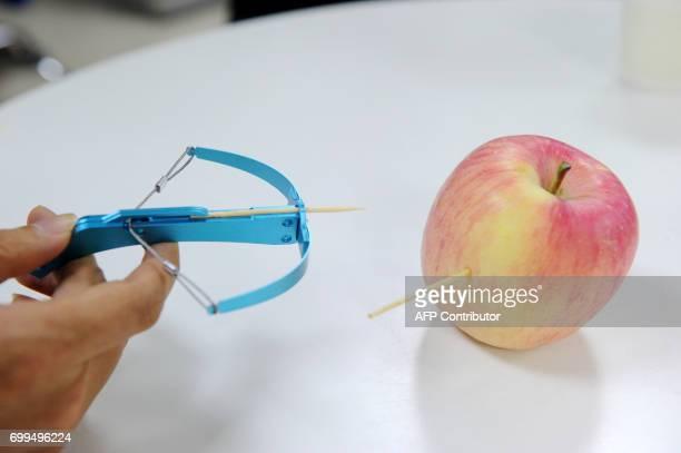 This photo taken on June 20 2017 shows a man demonstrating a toothpick crossbow in Chengdu in China's southwest Sichuan province Handheld crossbows...